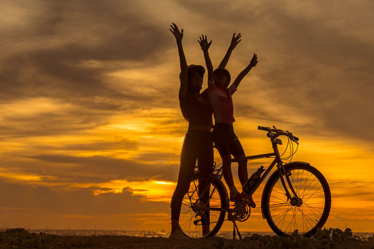 Full length of woman with bicycle in background during sunset