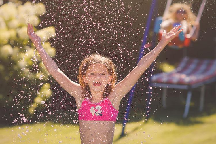 Portrait Of Girl Splashing Water At Yard