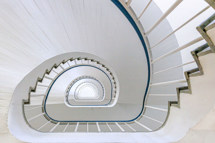 A white staircase circling towards the top of a building in Stockholm, Sweden Staircase Steps And Staircases Architecture Spiral Built Structure Spiral Staircase Railing Indoors  Pattern No People Design Diminishing Perspective High Angle View Day White Color Directly Below Absence Directly Above Building Building Feature Stockholm, Sweden