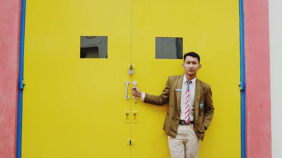 Portrait of smiling young man standing against yellow door