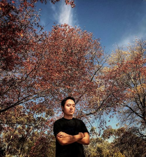 Portrait of young man standing by tree against cloudy sky during autumn.