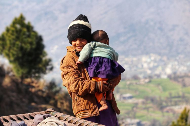 Portrait of girl carrying sister against mountain