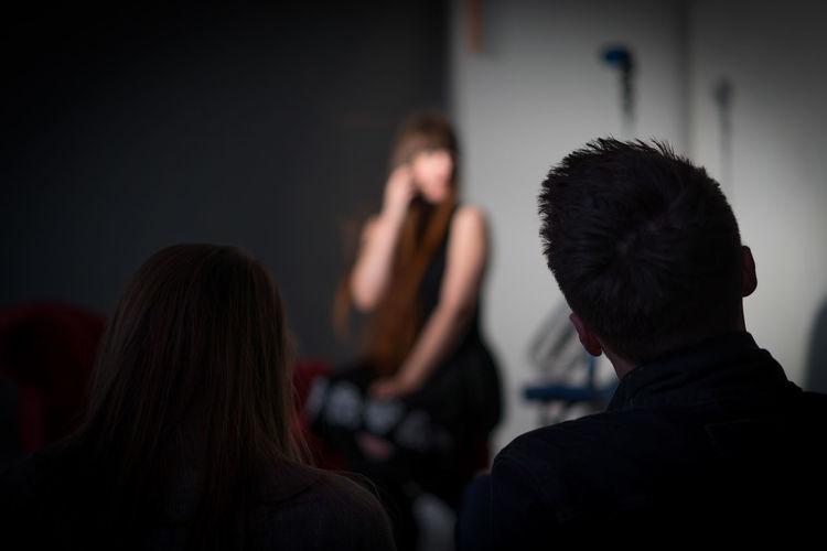 Rear view of people sitting in studio