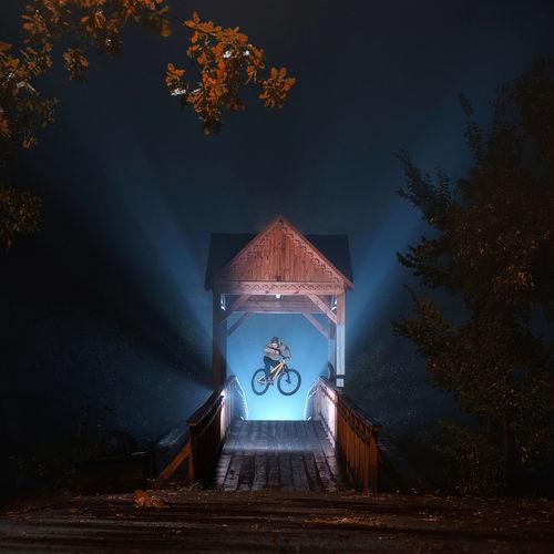 Illuminated mtb riderjumping against foggy sky at night