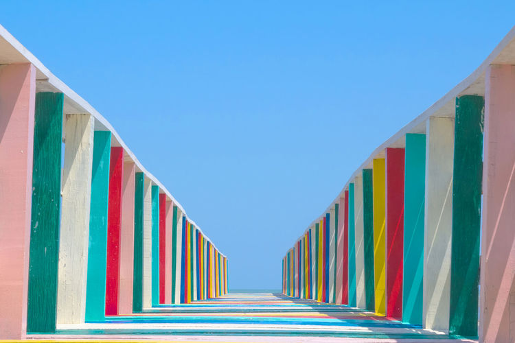 Low angle view of multi colored wooden footbridge against sky