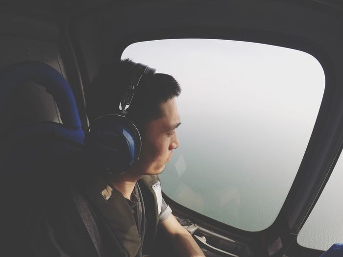 Flying over the ocean Ocean Sea Helicopter Mode Of Transportation Transportation Vehicle Interior One Person Real People Window Headshot Young Adult Lifestyles Portrait Sitting Leisure Activity Travel Looking The Photojournalist - 2018 EyeEm Awards