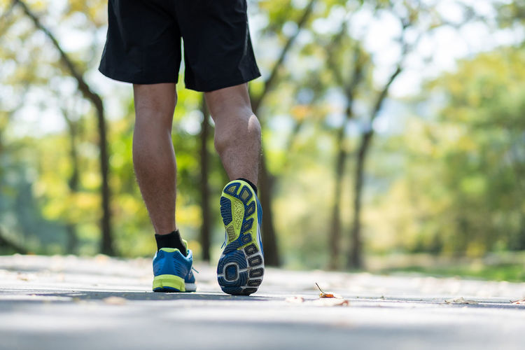 young fitness man legs walking in the park outdoor, male runner running on the road outside, asian athlete jogging and exercise on footpath in sunlight morning. Sport,healthy and wellness concepts
