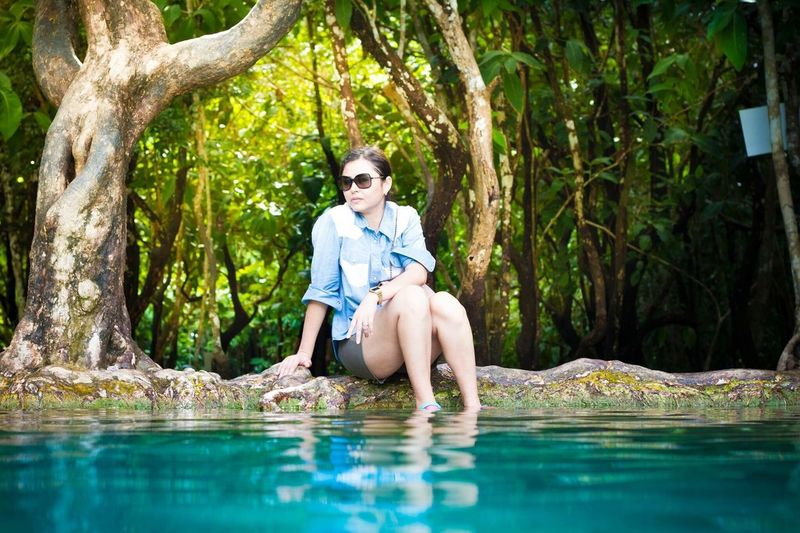 Young woman sitting by turquoise pond against trees
