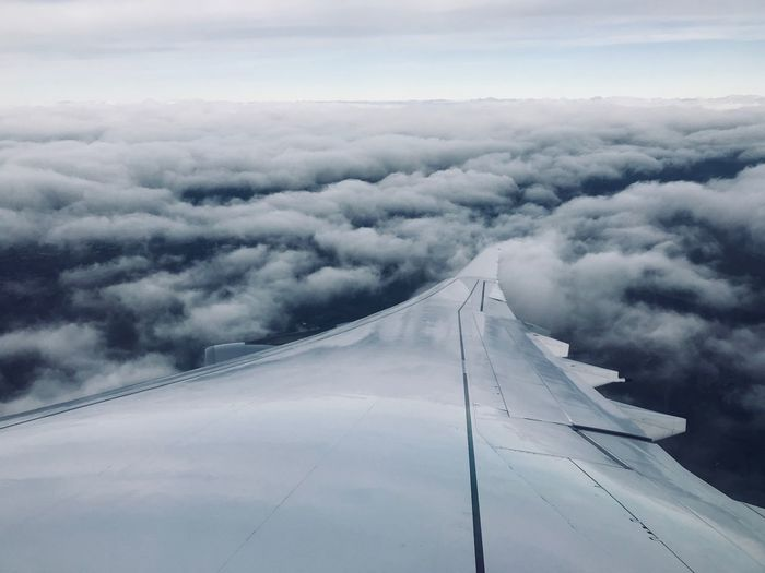 Close-Up Of Airplane Wing Against Cloudy Sky