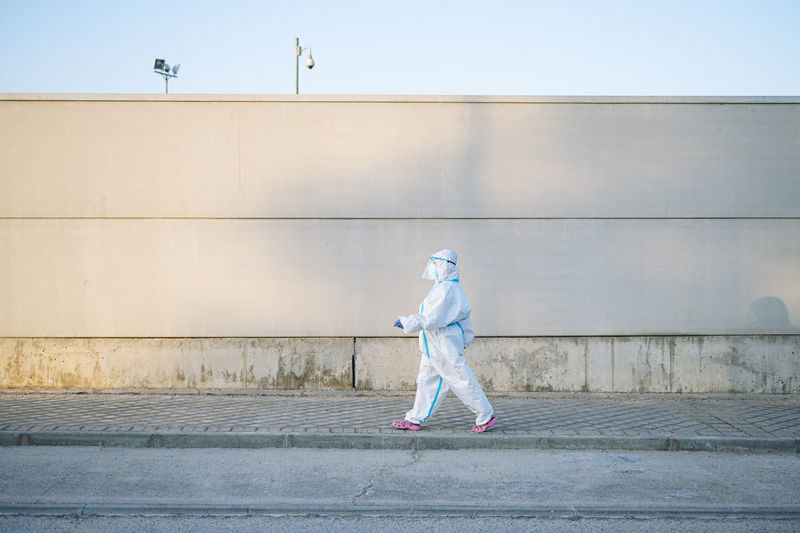 Full length side view of man walking against wall