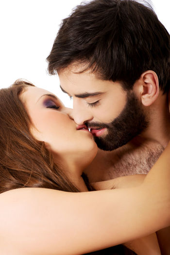 Romantic Young Couple Kissing Against White Background