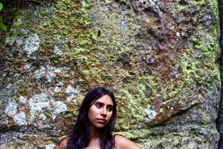 Close-up of woman standing against mossy wall