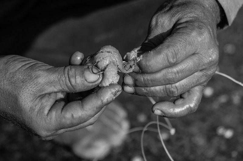 Close-up of hands preparing fishing tackle
