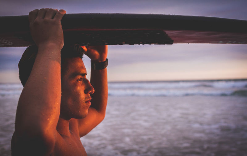 Close-up of man carrying surfboard on head while standing at beach