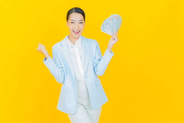 Portrait of woman with umbrella standing against yellow background