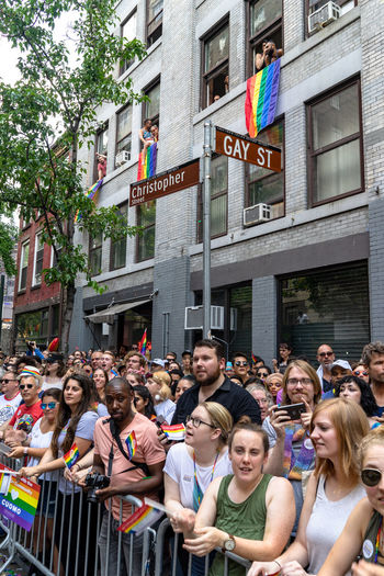 Crowd gathers to watch the Gay Pride Parade held in New York City 2018. Christopher Street Day Gay Pride Parade 2018 Gay Street New York Building Exterior Crowd Flag Gay Pride Parade Lgbt Lgbtq Love Is Love Parade Rainbow Street Sign Watching