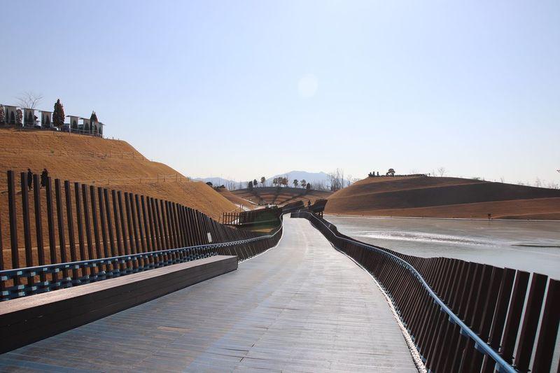 Footbridge and mountains against blue sky