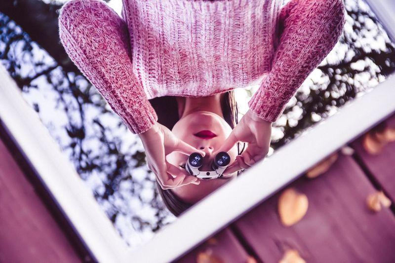 Woman with binocular reflecting on mirror