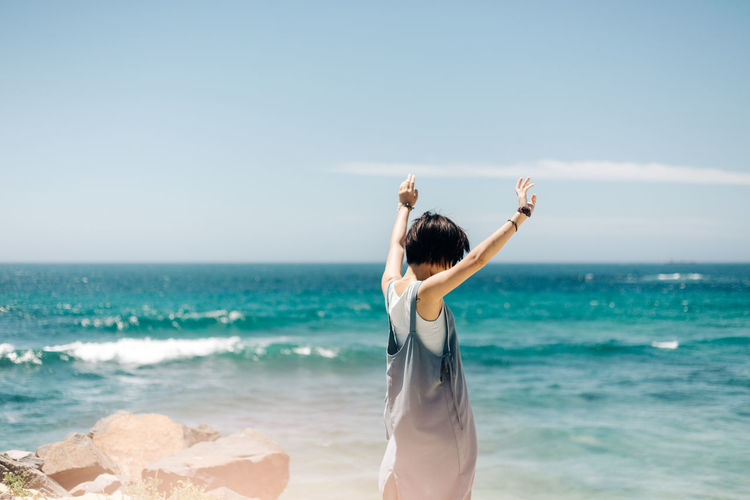 Sea Beach Water Sky Land Leisure Activity Horizon Over Water Lifestyles Human Arm Women Adult Beauty In Nature Standing Horizon Scenics - Nature Nature Real People Day One Person Arms Raised Hairstyle Outdoors Travel Destinations People Portrait