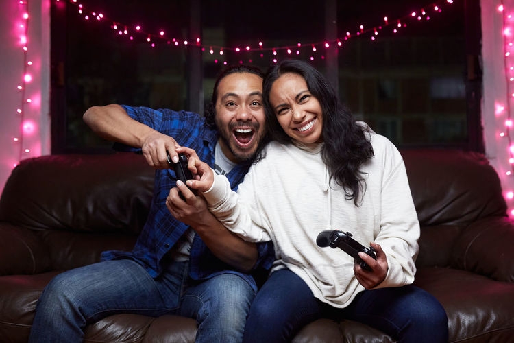 Young couple sitting on sofa at night