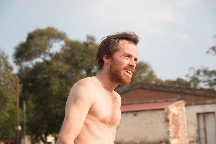 Portrait of shirtless bearded man smiling