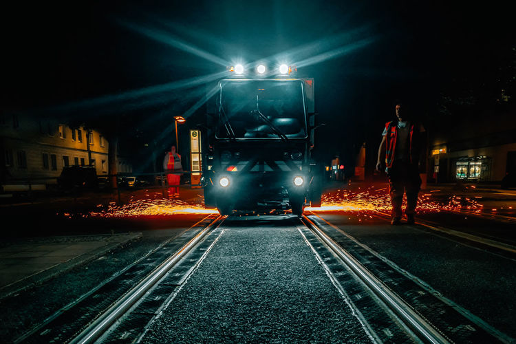 Train on illuminated railroad tracks at night