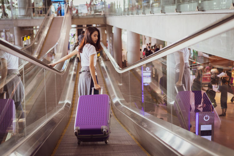 Asian woman traveler walking on escalator to airplane after booking ticket flight at airport with carrying,backpack,suitcase luggage for transport travel international vacation time. Escalator Women Lifestyles Females Shopping Young Women Travel Beautiful Woman Woman Waiting Booking Business Holiday Walking Summer Departure Transfer Tourist Tourism Tour Technology Maps Girl Looking Luggage Airplane Suitcase Passenger Terminal Ticket Airline Passport Plane Trip Bag Airport Lifestyle Flight Journey Vacation Happy International Arrival Asian  Fashion People Standing Leisure Activity Indoors  Adult