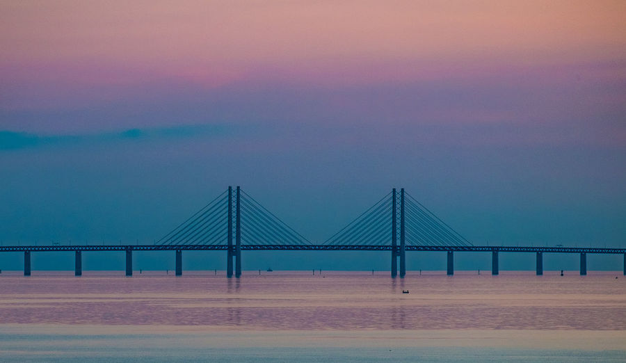 Suspension bridge over sea against sky during sunset