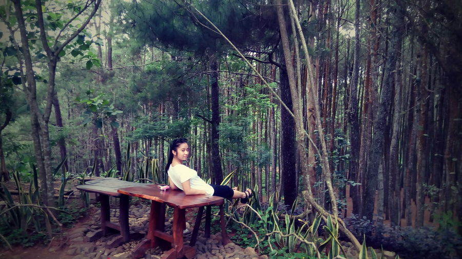 Teenage girl reclining on table against trees in forest