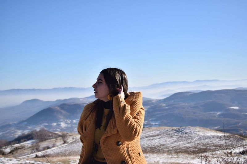 Young woman looking away against blue sky at mountains