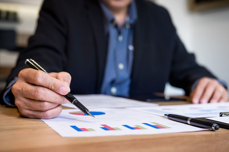 Midsection of businessman working over graph at desk