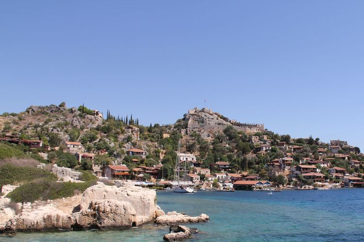 Buildings by sea against clear blue sky