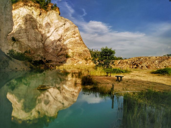Rock formation by calm lake against sky