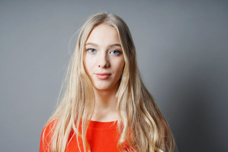 Gray Background Blond Hair Portrait Studio Shot Long Hair Looking At Camera One Person Indoors  Front View Beautiful Woman Young Adult Blonde Girl Woman Real People People person Teenager Teen Red Sweater Casual Clothing Youth Headshot Women Beauty