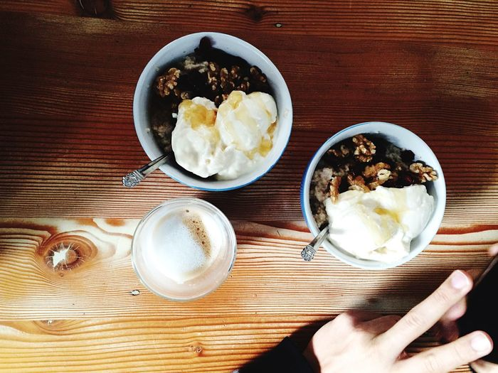 Bowls of deserts served with coffee on table
