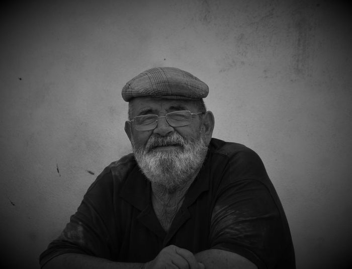 Portrait Of Senior Man Against Wall