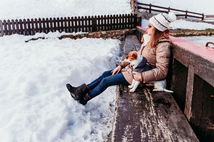 Cheerful woman with dog sitting on bench during winter