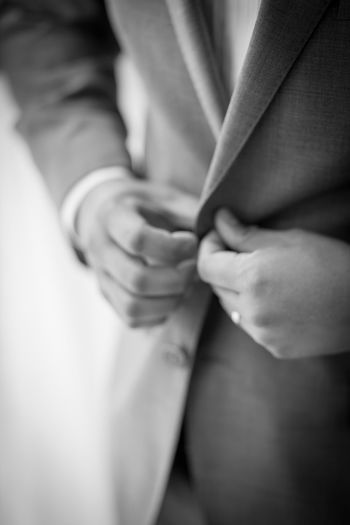 Midsection of man buttoning suit