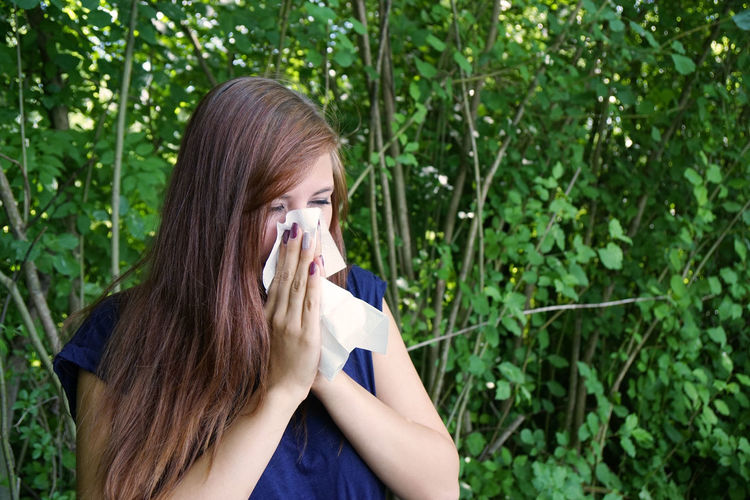 Young woman by plants blowing nose