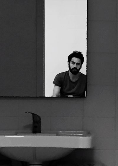 Reflection of man on mirror in bathroom