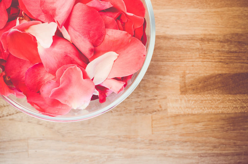 High angle view of red rose petals in container on table