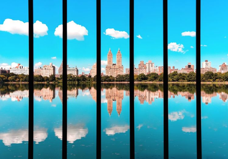 Reflection of buildings in reservoir against blue sky
