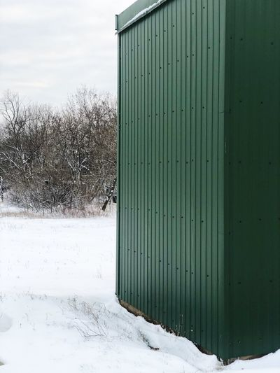Snow covered field by building