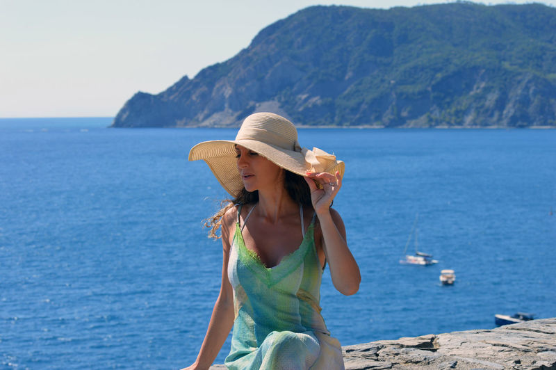 Woman wearing hat against sea and mountains against sky