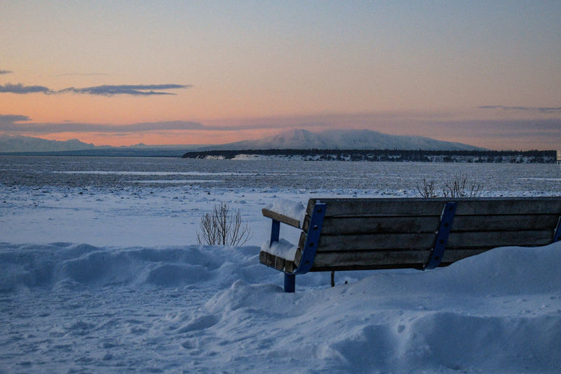 Empty bench on snow covered shore against sky during sunset