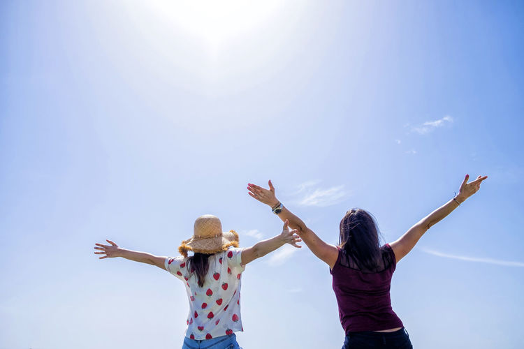Rear view of two young woman sitting on a fence with arms raised against blue sky Sky Human Arm Women Togetherness Real People Rear View Standing Arms Raised Two People Lifestyles Casual Clothing Leisure Activity Limb Bonding Adult Sunlight Friendship Three Quarter Length Nature Positive Emotion Hairstyle Human Limb Lens Flare Sister