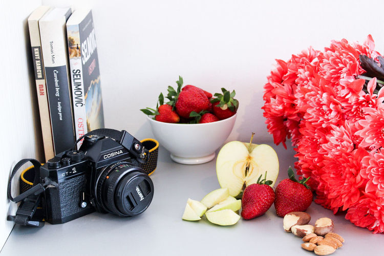 Close-up of strawberries and fruits on table against white background