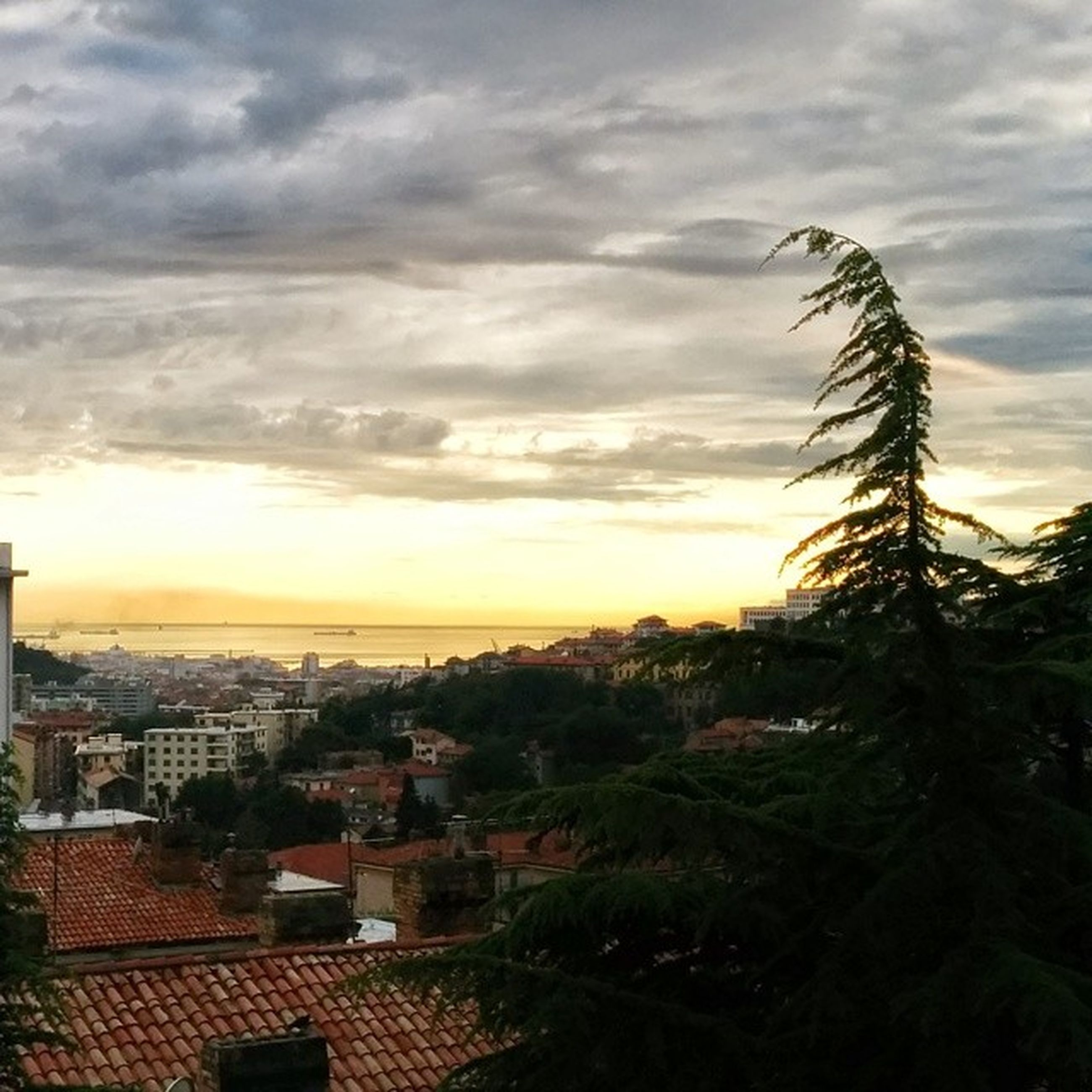 sky, building exterior, architecture, built structure, cloud - sky, sunset, cloudy, cityscape, city, cloud, residential structure, high angle view, residential building, house, residential district, tree, horizon over water, nature, sea, scenics