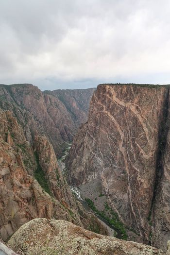 Portrait of deep canyon, a river, and steep cliffs in Colorado Cliffs Black Canyon Of The Gunnison National Park River Colorado Sky Cloud - Sky Landscape Environment Day Tranquil Scene Scenics - Nature Non-urban Scene Mountain Rock No People Land Geology Nature Tranquility Solid Travel Destinations Beauty In Nature Rock - Object Outdoors The Great Outdoors - 2018 EyeEm Awards