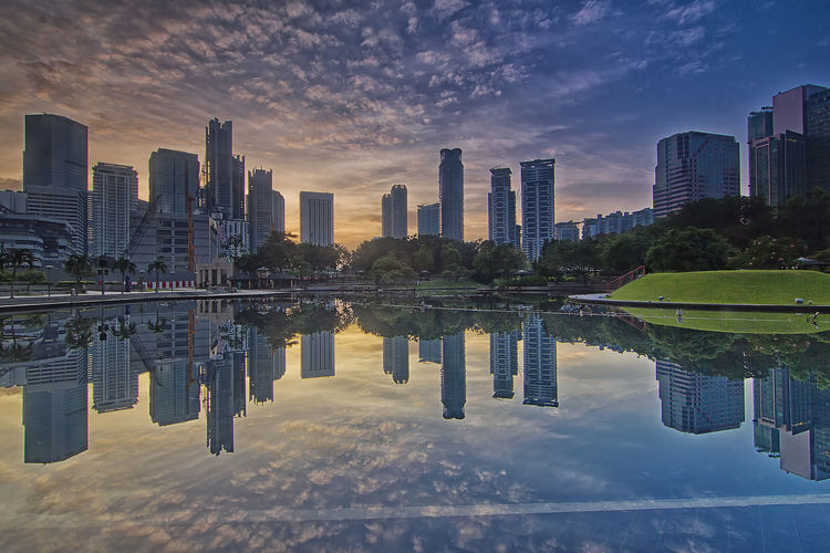 Sunrise view of high rise skyscrapper with reflection from Symphony lake, KLCC Architecture Building Exterior Built Structure City Cityscape Cloud - Sky Day Downtown District Financial District  Modern Nature No People Outdoors Reflecting Pool Reflection River Sky Skyscraper Sunset Tall - High Travel Destinations Tree Urban Skyline Water Waterfront